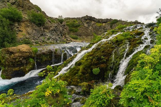 Rzeka przepływająca przez nierówny teren, tworząc wiele małych wodospadów