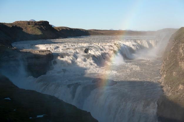 Rzeka przepływająca przez skały, tworząc wodospad i tęcza
