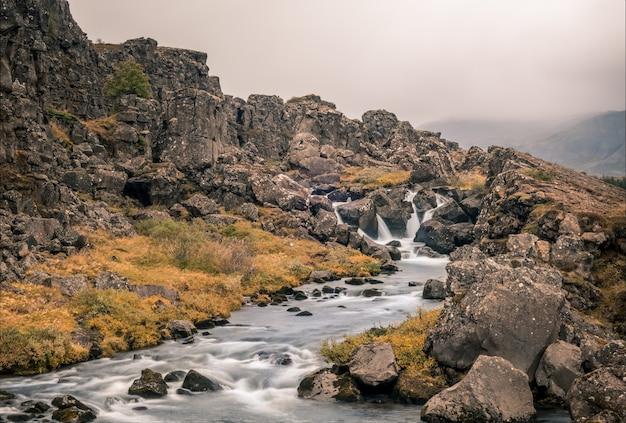 Rzeka przepływająca przez skały uchwycone w parku narodowym thingvellir na islandii