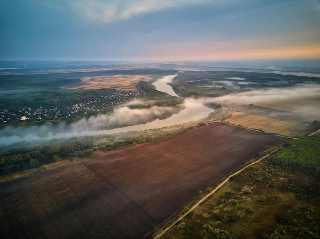 Rzeka scenerii we wczesnych godzinach porannych. w oddali chata i drzewo zakryte mistyczną mgłą, bardzo ciche i spokojne. republika mołdawii.
