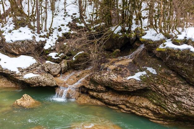 Rzeka w górach. górzysty teren. zdjęcie na długiej ekspozycji, pochmurny dzień. wodospady w górach w lesie, zimowy krajobraz górskich rzek