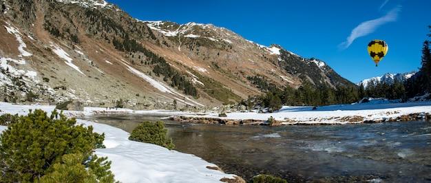 Rzeka w ośnieżonych górach pirenejów z żółtym balonem