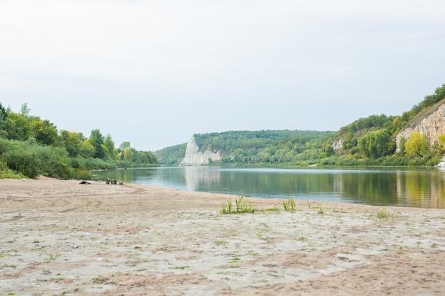 Rzeka w skalistych brzegach porośnięta zielenią i pustą plażą.