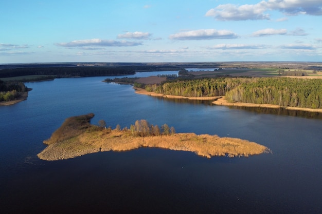Rzeka wyspa i las z lotu ptaka. zbiornik retencyjny, jezioro. zdjęcia lotnicze wiosennego krajobrazu z błękitnym niebem i białymi chmurami, płaski teren