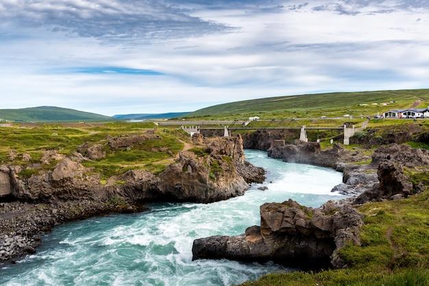 Rzeka z godafoss falls, akureyri, islandia, otoczona ogromnymi skałami i betonowym mostem
