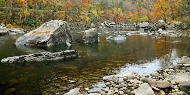 Rzeka z kamieniami w jesiennych górach