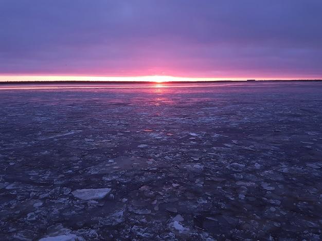 Rzeka z popękanymi kryształkami lodu w kolorowym mroźnym zachodzie słońca w kolorach fioletowym i różowym.