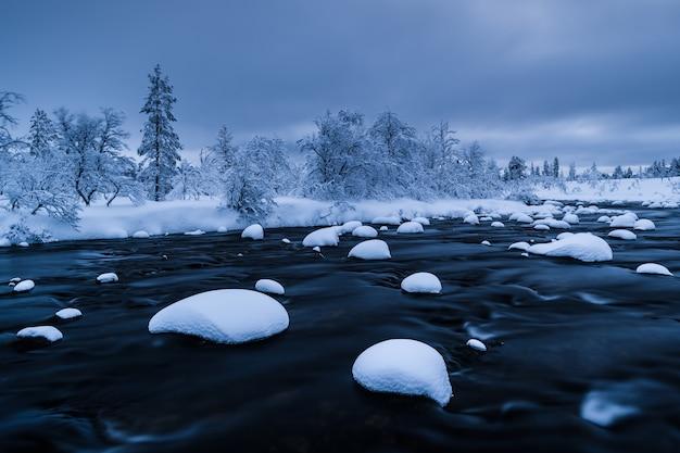 Rzeka ze śniegiem w nim i las w pobliżu pokryty śniegiem w zimie w szwecji