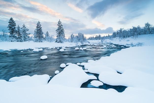 Rzeka ze śniegiem w środku i las w pobliżu pokryte śniegiem zimą w szwecji
