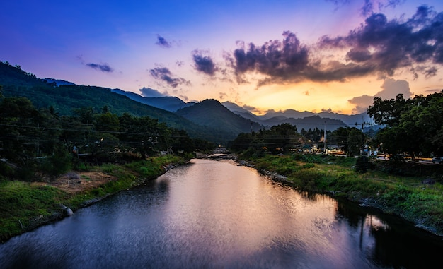 Rzeki kamień i drzewo w zmierzchu lub wschodzie słońca