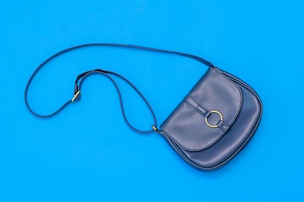 Rzemienna błękitna kobiety torba na błękitnym tle. widok z góry. leżał płasko.