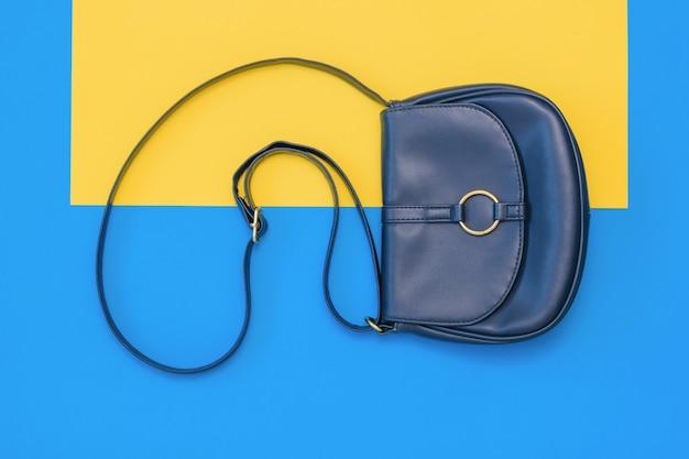 Rzemienna błękitna kobiety torba na żółtym i błękitnym tle. minimalizm w rzeczach kobiet.