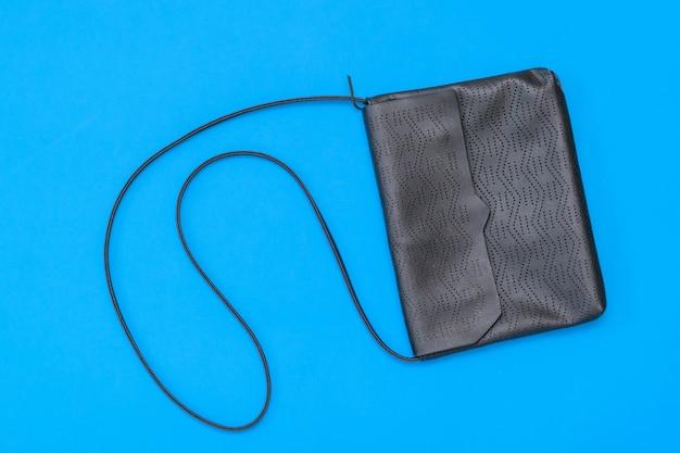 Rzemienna murzynek torba na błękitnym tle. widok z góry. leżał płasko.