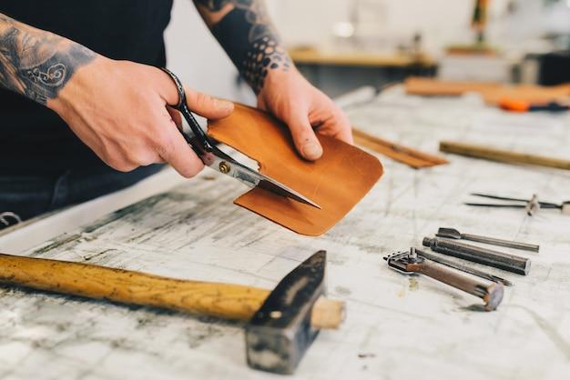 Rzemienni rzemioseł narzędzia na drewnianym tle. biurko z rzemieślniczą skórą