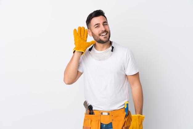Rzemieślnicy lub elektryk mężczyzna na białym ścianie coś nasłuchuje
