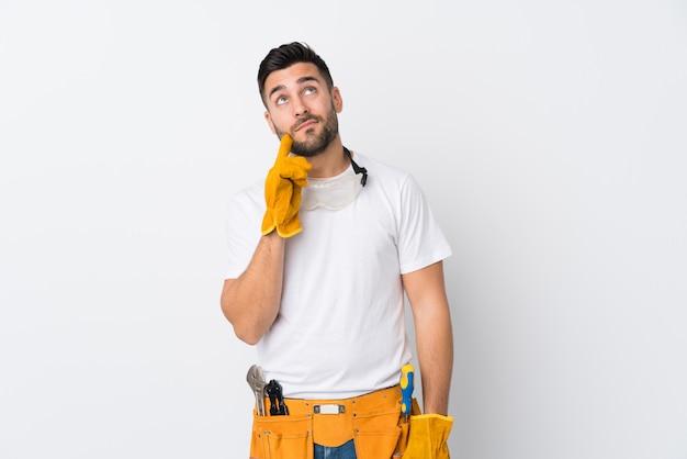 Rzemieślnicy lub elektryk mężczyzna na białym tle ściany myślenia pomysł