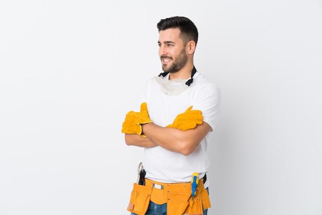 Rzemieślnicy lub elektryk mężczyzna na pojedyncze białe ściany, patrząc z boku