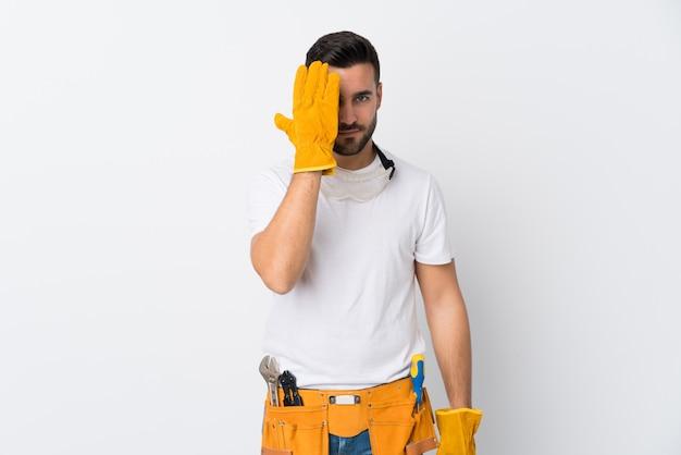 Rzemieślnicy lub elektryk mężczyzna na pojedyncze białej ścianie zasłaniając oko ręką