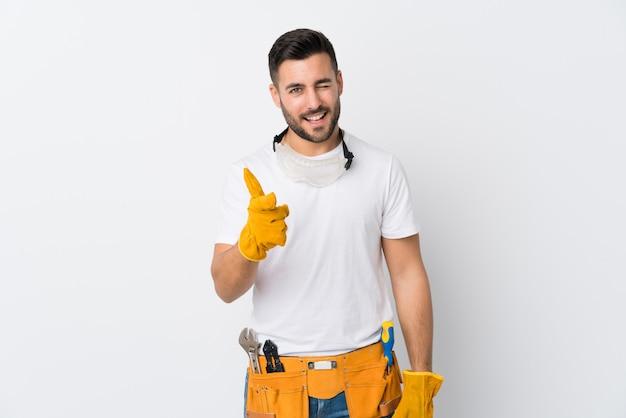 Rzemieślnicy lub elektryk nad odosobnionymi białymi ścianami wskazują na ciebie palcem