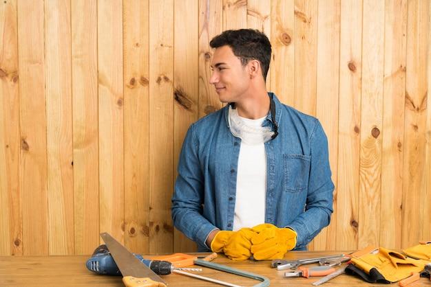 Rzemieślnicy mężczyzna nad drewnianym tłem patrzeje strona