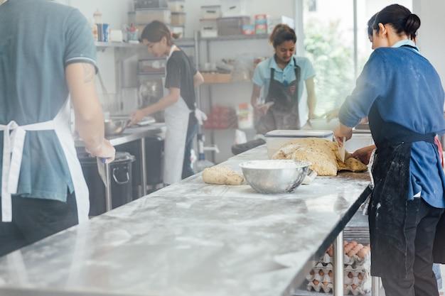 Rzemieślnicy robią chlebowi na odgórnym aluminiowym stole z mąką nad stołem.