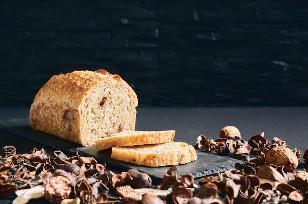 Rzemieślniczy chleb pomidorowy z kilkoma plasterkami pokrojonymi na łupek, ozdobiony orzechami i suszonymi liśćmi