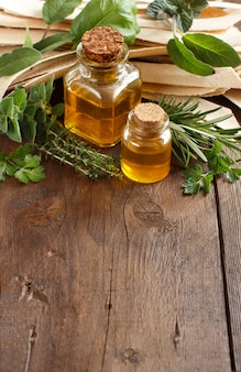 Rzemieślniczy makaron pełnoziarnisty, oliwa z oliwek i zioła na starym drewnianym stole