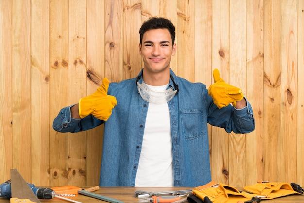 Rzemieślnik człowieka na ścianie drewna podając kciuki gest