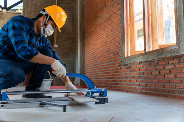 Rzemieślnik, glazurnik, glazurnik przemysłowy, pracownik budowlany pracujący z urządzeniami do cięcia płytek podłogowych na placu budowy