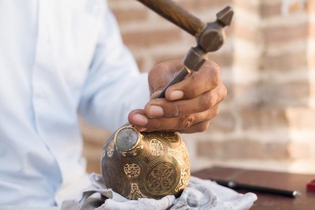 Rzemieślnik grawerujący wzory na dzbanku. mistrzowie azji środkowej. ręczne wybijanie miedzi