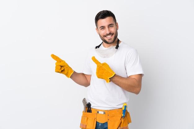 Rzemieślnik lub elektryk mężczyzna na białym palcem wskazującym na białej ścianie