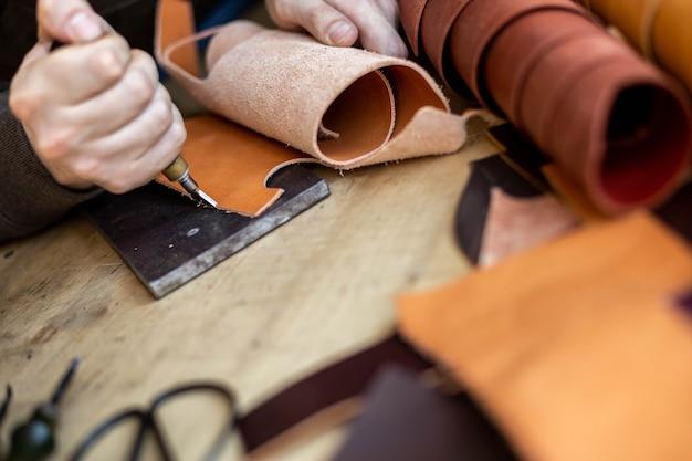 Rzemieślnik maszyny krawędź naturalnego przedmiotu obrabianego używają profesjonalnego warsztatu skórzanego z kręconymi nożami;