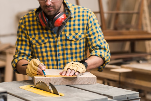 Rzemieślnik mierzy drewnianą deskę z władcą