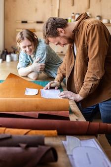 Rzemieślnik odpakowujący pakunek z naturalnego materiału pracujący w kaletniczym warsztacie kaletniczym