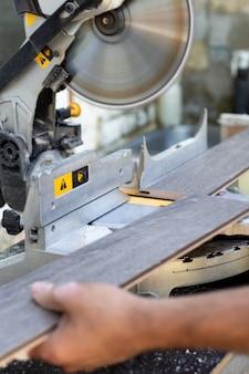 Rzemieślnik piłuje drewnianą deskę na piły tarczowej. wykonywanie mebli profesjonalnym narzędziem.