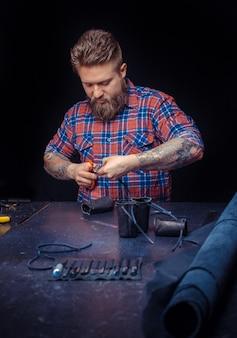 Rzemieślnik pracujący ze skórą obrabia przedmiot ze skóry w miejscu pracy.