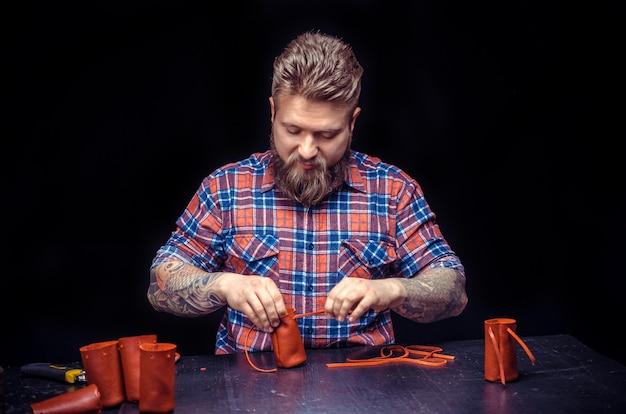 Rzemieślnik pracujący ze skórą przetwarzający skórzany przedmiot w swoim studio skórzanym