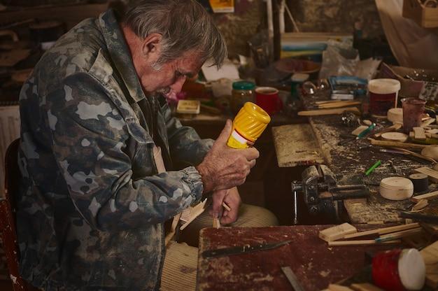 Rzemieślnik przykleja kawałki drewna do modelu, aby wykonać drewniane przedmioty w warsztacie. koncepcje dotyczące sztuki, umiejętności i hobby