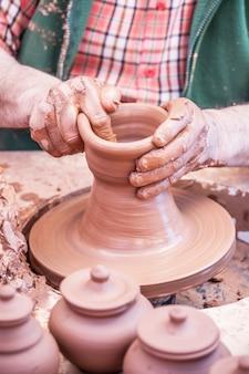 Rzemieślnik robi glinianemu garnkowi z rękami