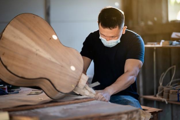 Rzemieślnik robiąc gitarę na stole z drewna, koncepcja pracy capenter