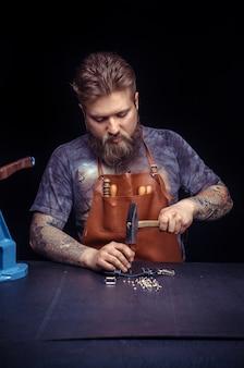 Rzemieślnik skór tworzy nowy produkt skórzany w swojej garbarni.