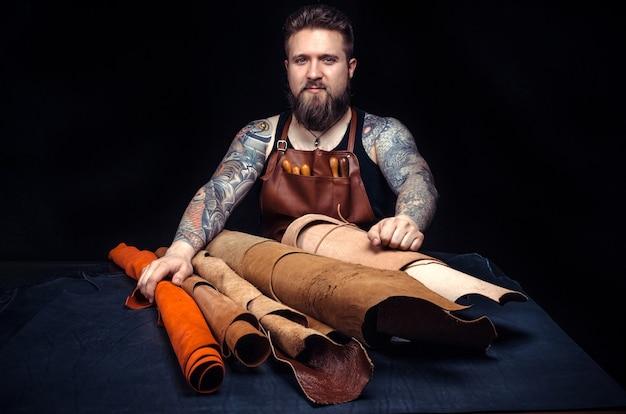 Rzemieślnik skór zajmujący się obróbką galanterii skórzanej w swojej garbarni