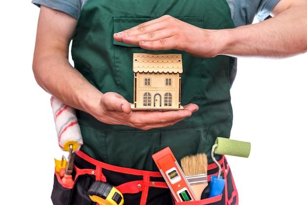 Rzemieślnik trzymający drewniany model domu na białym tle