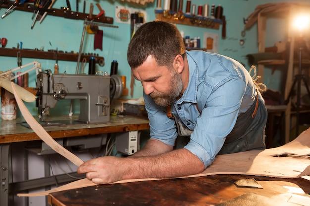 Rzemieślnik w fartuchu pracuje ze skórą przy warsztatem