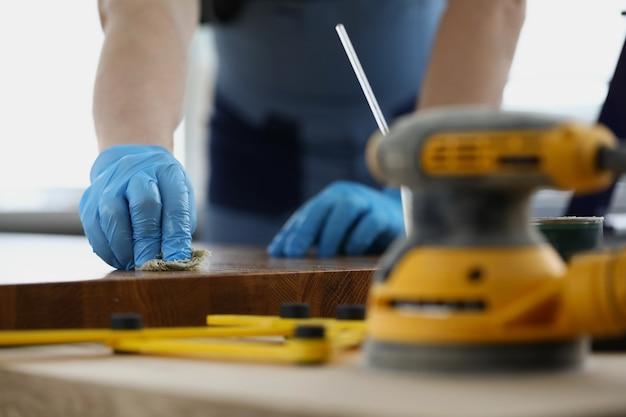 Rzemieślnik w rękawiczkach czyści drewniane powierzchnie płynem ochronnym