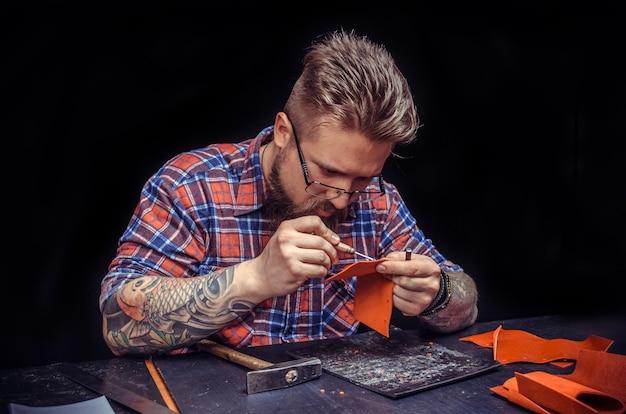 Rzemieślnik wycina galanterię skórzaną w sklepie skórzanym