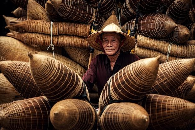 Rzemieślnik wykonujący bambusową pułapkę na ryby w starej wiosce, hung yen, wietnam