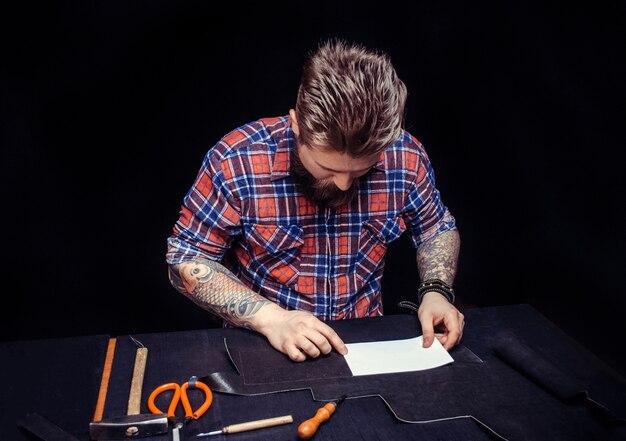 Rzemieślnik Wykonuje W Warsztacie Obróbkę Skór Dla Nowego Produktu. Premium Zdjęcia