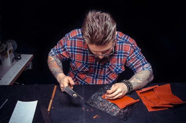 Rzemieślnik z brodą, który w swoim sklepie wykuwa dziury w skórzanym elemencie