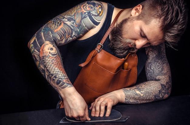 Rzemieślnik zajmujący się skórą skupił się na swojej pracy w pracowni kaletniczej.